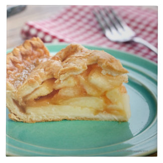 Slice of fresh baked apple pie on plate large square tile