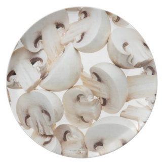 Sliced button mushrooms (agaricus bisporus), on plate