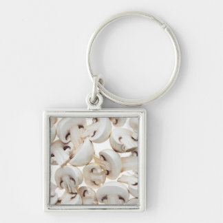 Sliced button mushrooms (agaricus bisporus), on Silver-Colored square key ring