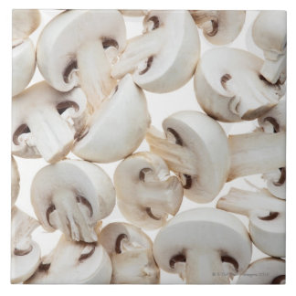 Sliced button mushrooms (agaricus bisporus), on tile