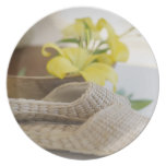 Slippers beside a wooden bowl with yellow lilies dinner plates