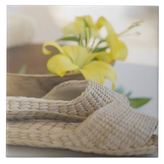 Slippers beside a wooden bowl with yellow lilies large square tile