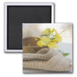Slippers beside a wooden bowl with yellow lilies refrigerator magnet