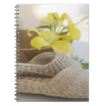 Slippers beside a wooden bowl with yellow lilies spiral note book