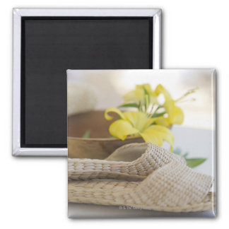 Slippers beside a wooden bowl with yellow lilies square magnet