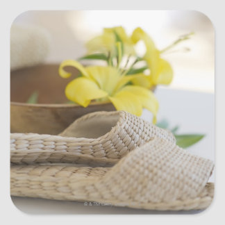Slippers beside a wooden bowl with yellow lilies square sticker
