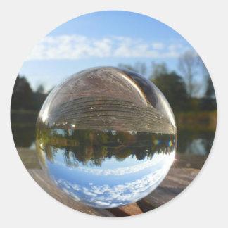 Small sea seen through a crystal ball round sticker
