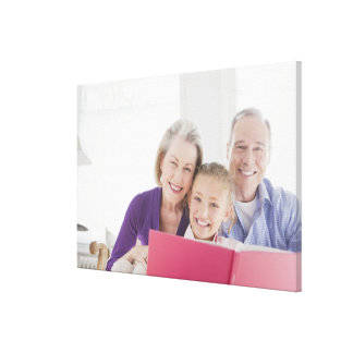 Smiling grandparents reading cookbook with canvas print