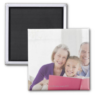 Smiling grandparents reading cookbook with magnet