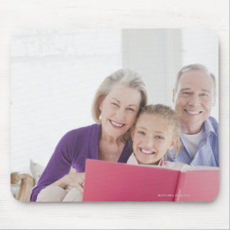 Smiling grandparents reading cookbook with mouse mat