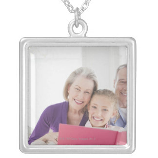 Smiling grandparents reading cookbook with silver plated necklace