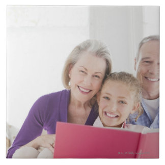 Smiling grandparents reading cookbook with tile