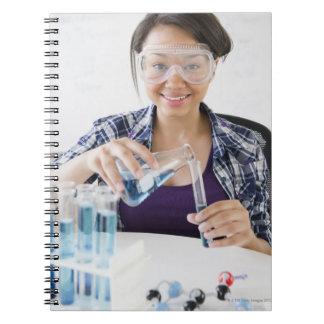 Smiling mixed race teenage girl conducting notebook