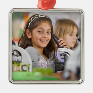 Smiling students peering into microscopes in christmas ornament