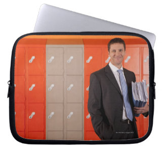 Smiling teacher holding paperwork near school laptop sleeve