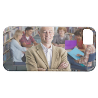 Smiling teacher standing in school library with barely there iPhone 5 case