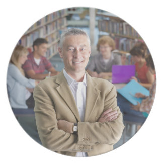 Smiling teacher standing in school library with party plates