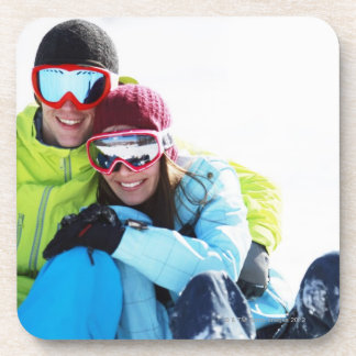 Snowboarder couple sitting on snow coaster