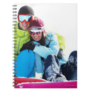 Snowboarder couple sitting on snow notebook