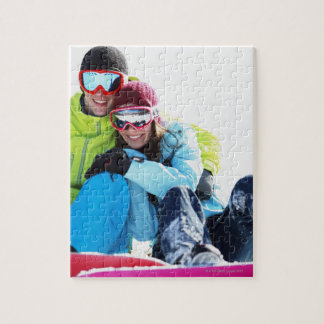 Snowboarder couple sitting on snow puzzle