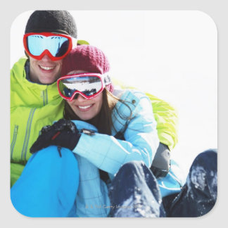Snowboarder couple sitting on snow square sticker