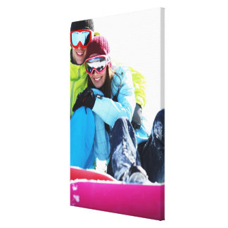 Snowboarder couple sitting on snow stretched canvas prints