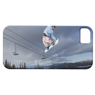 Snowboarder jumping in mid-air doing a backside case for the iPhone 5