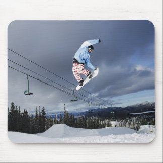 Snowboarder jumping in mid-air doing a backside mouse mat