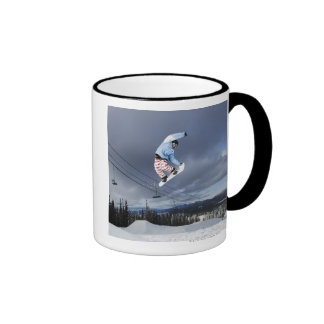 Snowboarder jumping in mid-air doing a backside coffee mugs