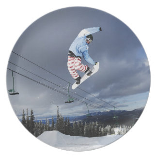 Snowboarder jumping in mid-air doing a backside dinner plate