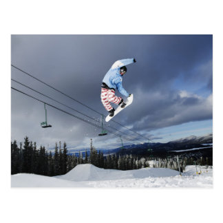 Snowboarder jumping in mid-air doing a backside postcard