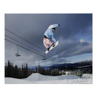 Snowboarder jumping in mid-air doing a backside poster