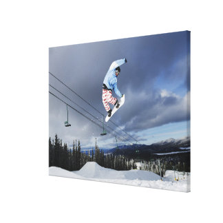 Snowboarder jumping in mid-air doing a backside stretched canvas print