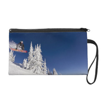Snowboarding action at Whitefish Mountain Resort Wristlet Clutch