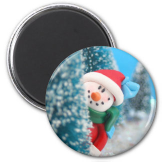 Snowman hiding or peeking from behind a tree 6 cm round magnet