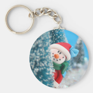 Snowman hiding or peeking from behind a tree basic round button key ring