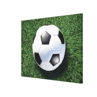 Soccer ball on green grass, close-up canvas print