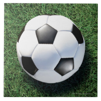 Soccer ball on green grass, close-up large square tile