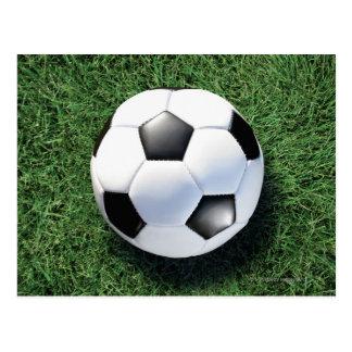 Soccer ball on green grass, close-up postcard