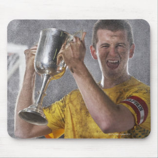 Soccer captain holding up trophy cup on field mouse pad
