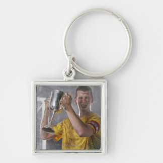 Soccer captain holding up trophy cup on field Silver-Colored square key ring