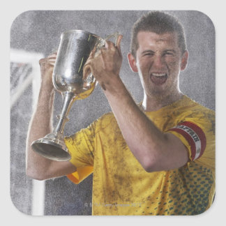 Soccer captain holding up trophy cup on field square sticker