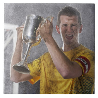 Soccer captain holding up trophy cup on field tile