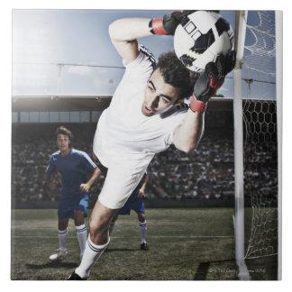 Soccer goalie catching soccer ball large square tile
