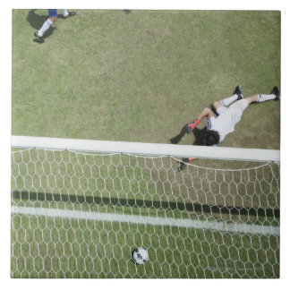 Soccer goalie missing soccer ball large square tile
