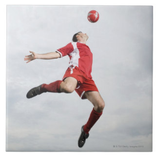 Soccer player and soccer ball in mid-air large square tile