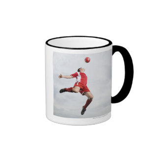 Soccer player and soccer ball in mid-air mug