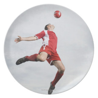 Soccer player and soccer ball in mid-air plate