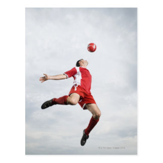 Soccer player and soccer ball in mid-air postcard