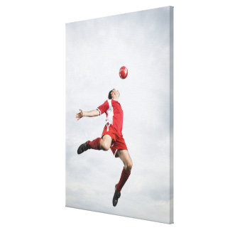 Soccer player and soccer ball in mid-air stretched canvas print